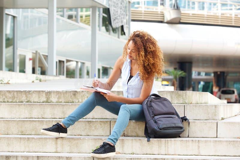 Weiblicher Seitenstudent, der auf dem Campus mit Stift und Buch sitzt stockbilder