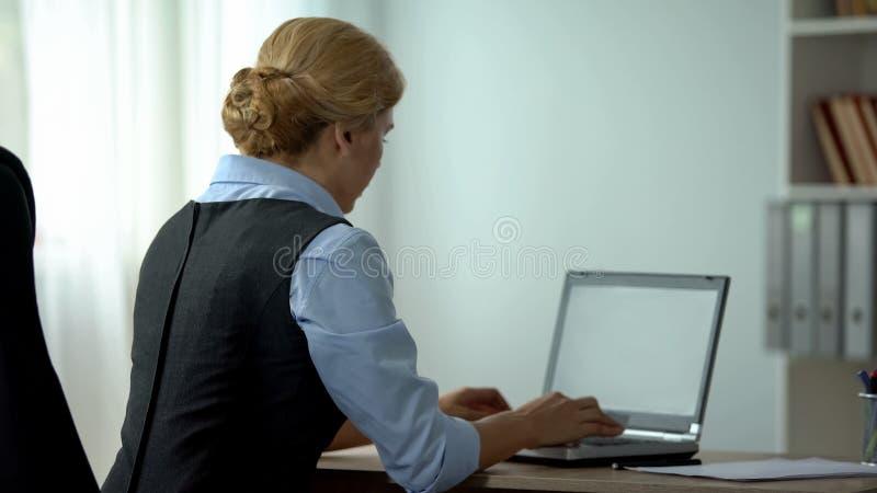 Weiblicher Sekretär, der auf Laptop im Büro, beschäftigter Arbeitszeitplan, Rückseitenansicht schreibt stockbild