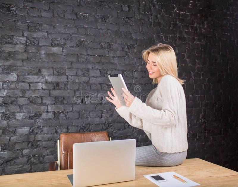 Weiblicher Sekretär, der die digitale Tablette, sitzend gegen Wand mit Kopienraum verwendet lizenzfreie stockbilder