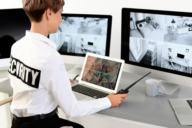Weiblicher Sicherheitsbeamte mit dem tragbaren Übermittler, der Hauptkameras überwacht lizenzfreie stockbilder