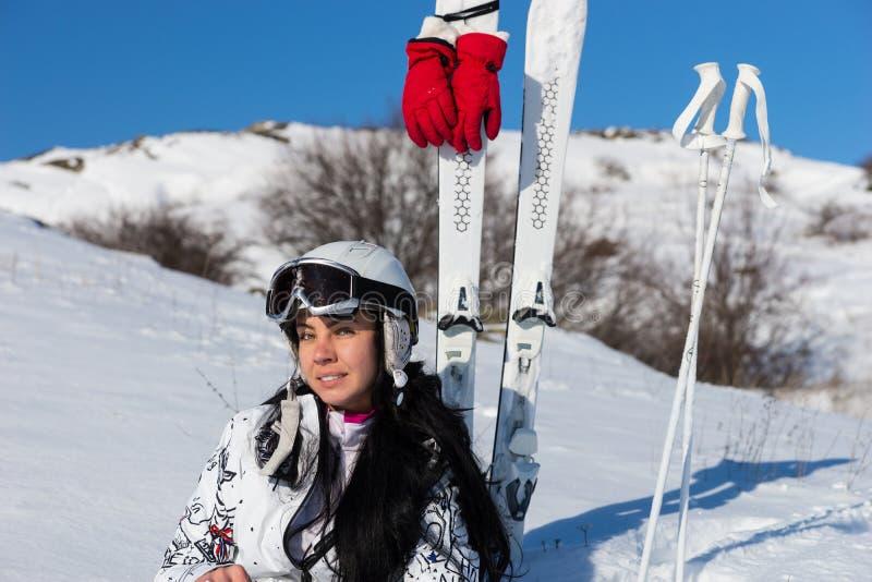 Weiblicher Skifahrer im Sturzhelm, der auf Hügel mit Skis sitzt stockfotos