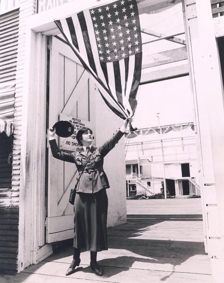Weiblicher Soldat, der amerikanische Flagge hält lizenzfreie stockbilder