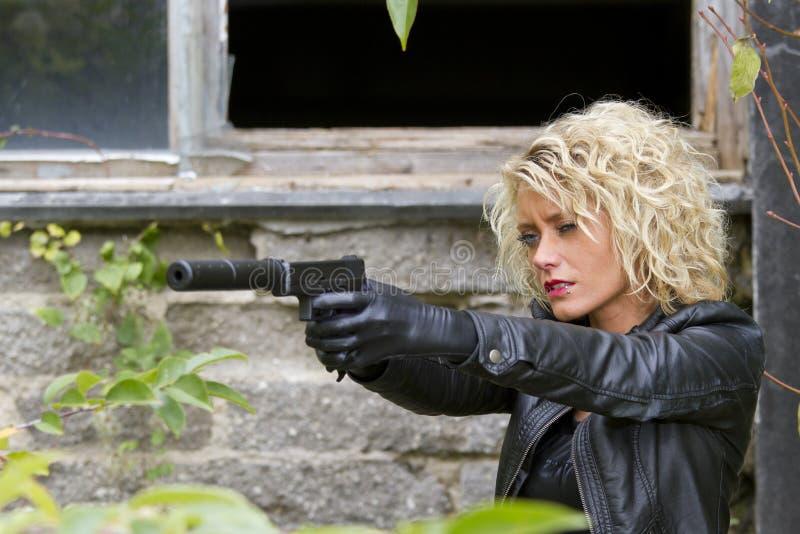 Weiblicher Spion mit Schalldämpferpistole stockfoto