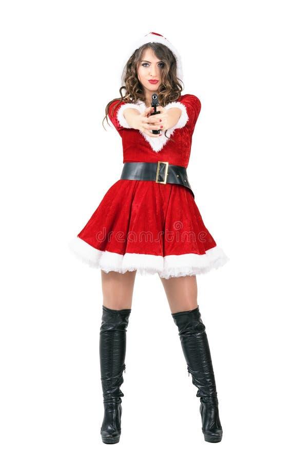 Weiblicher Spion verkleidet als Santa Claus mit dem Hoodie, der Gewehr auf Kamera abzielt stockfoto