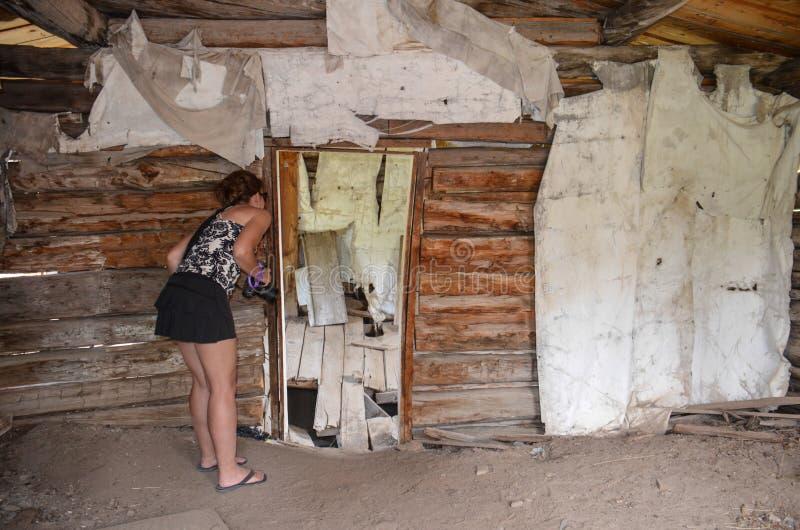 Weiblicher städtischer Forscher forscht einen verlassenen errichtenden Innenraum in den Bergmännern erfreuen Wyoming nach lizenzfreie stockbilder