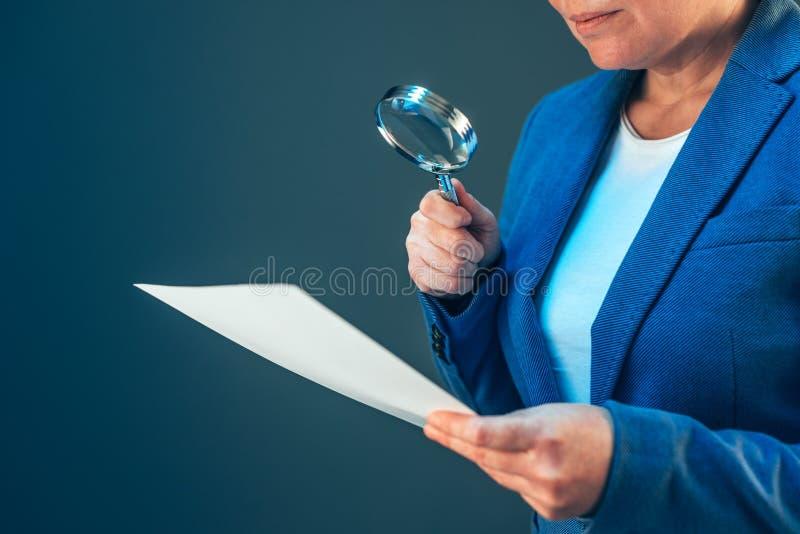 Weiblicher Steuerinspektor, der Dokument mit Lupe betrachtet lizenzfreie stockfotos