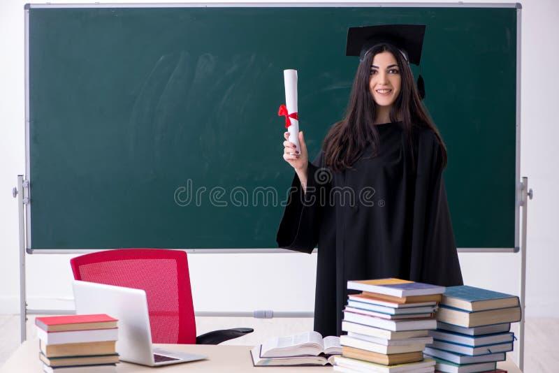 Weiblicher Student im Aufbaustudium vor gr?nem Brett stockfoto