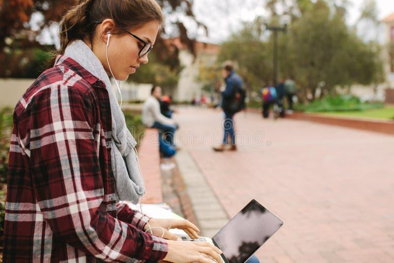 Weiblicher Student unter Verwendung des Laptops am Campus stockfotos