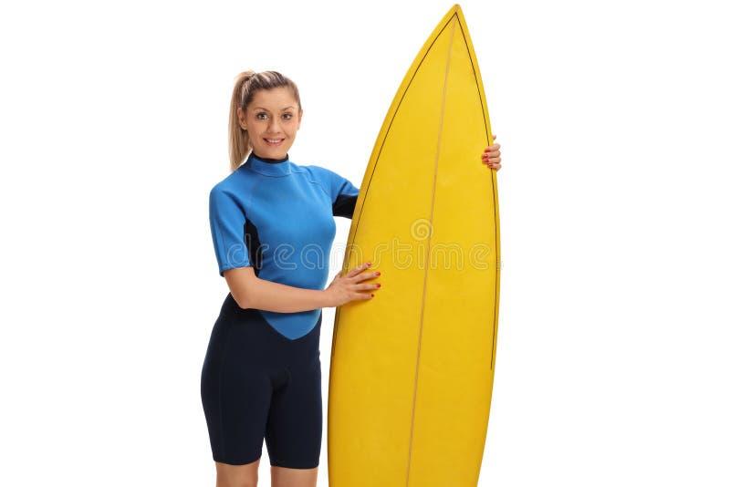 Weiblicher Surfer, der mit einem Surfbrett aufwirft lizenzfreie stockfotografie