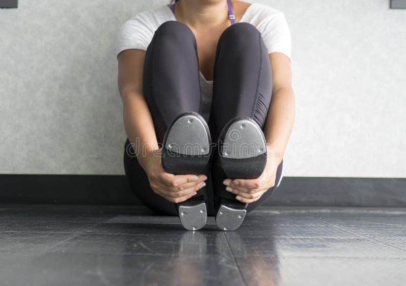 Weiblicher Tänzer, der in den Hahnklassenholding-Hahnschuhen sitzt lizenzfreie stockbilder