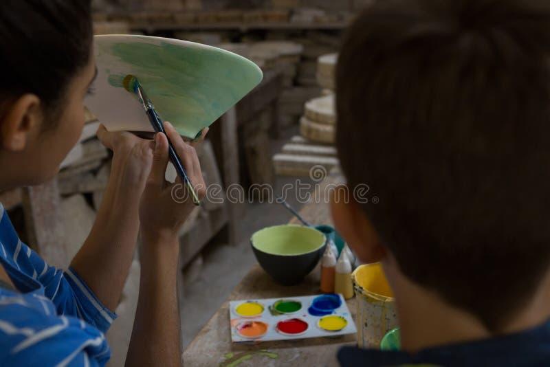 Weiblicher Töpfer, der ihren Sohn unterstützt, wenn eine Schüssel gemalt wird lizenzfreie stockbilder