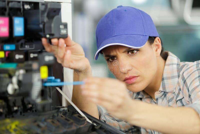 Weiblicher Techniker, der gesetzte Tinte in Plotter setzt lizenzfreies stockbild