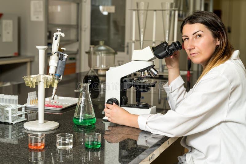 Weiblicher Techniker des Mittelalters Labor, dernahe bei Verbundmikroskop sitzt lizenzfreies stockbild