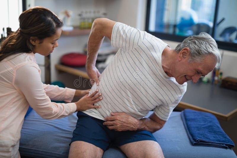 Weiblicher Therapeut, der zurück vom älteren männlichen Patienten sitzt auf Bett überprüft stockfotografie