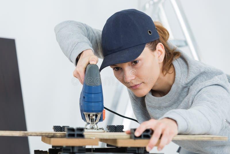 Weiblicher Tischler Cutting Wood With Tablesaw lizenzfreie stockfotografie
