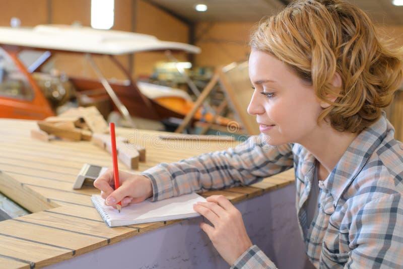 Weiblicher Tischler, der Anmerkungen macht stockfoto