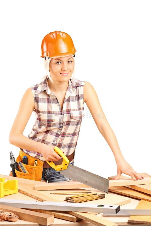 Weiblicher Tischler, der eine Planke mit einem Handsaw schneidet lizenzfreies stockbild