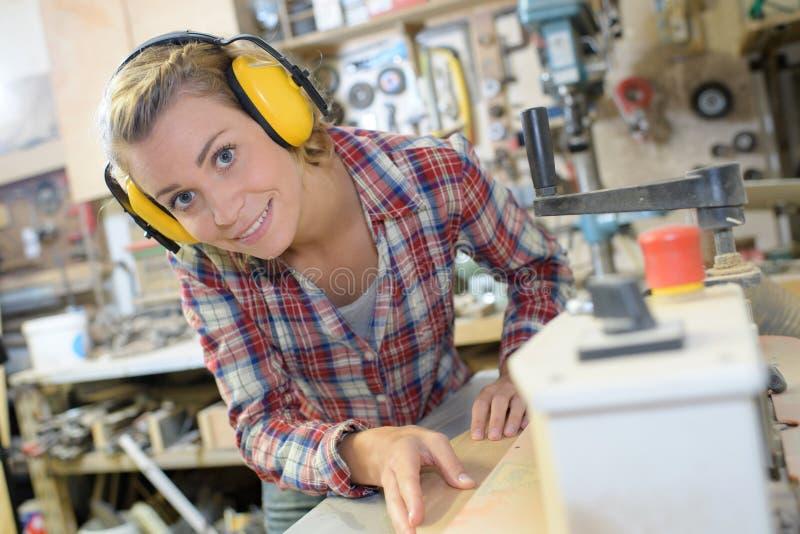 Weiblicher Tischler in der Schutzausrüstung, die Holz in der Werkstatt schneidet lizenzfreies stockfoto