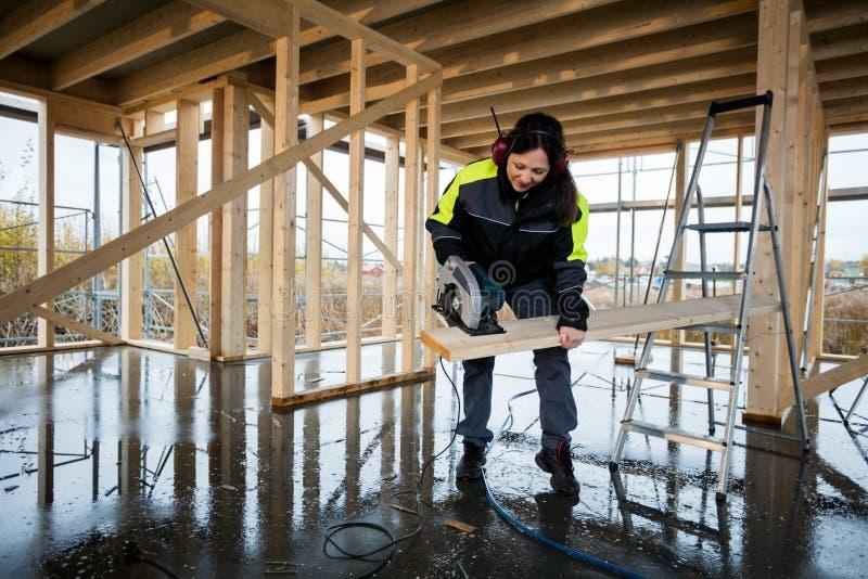 Weiblicher Tischler elektrisches Cutting Wood With sah am Bau stockfoto