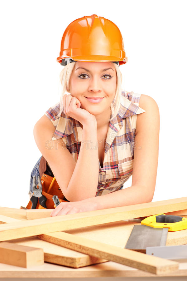 Weiblicher Tischler mit dem Sturzhelm, der am Arbeitsplatz aufwirft lizenzfreie stockbilder