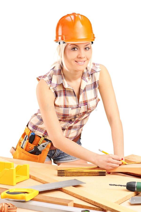 Weiblicher Tischler mit Sturzhelm bei der Arbeit stockfoto