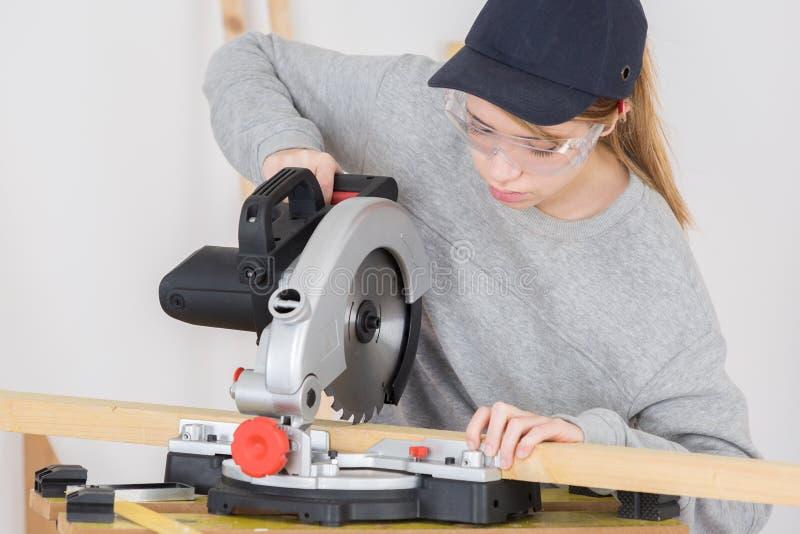 Weiblicher Tischler Using Circular Saw stockbild