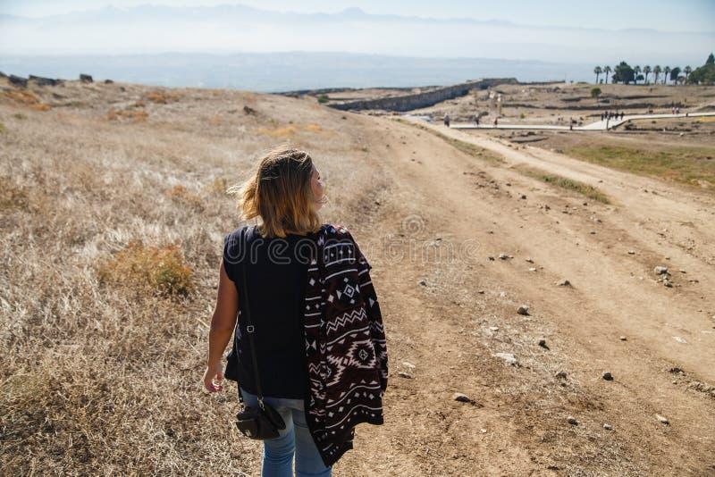 Weiblicher Tourist, der auf die Steppe geht Panoramische hintere Ansicht zu den Bergen Kopieren Sie Platz kleines blaues Auto auf lizenzfreie stockfotografie