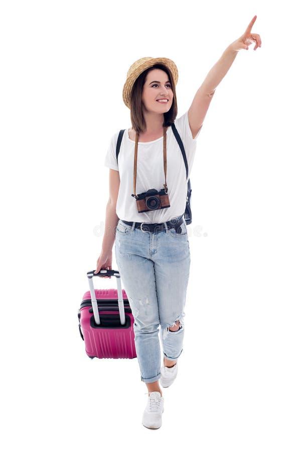 Weiblicher Tourist, der mit Koffer geht und auf etwas lokalisiert auf Weiß zeigt lizenzfreie stockfotografie