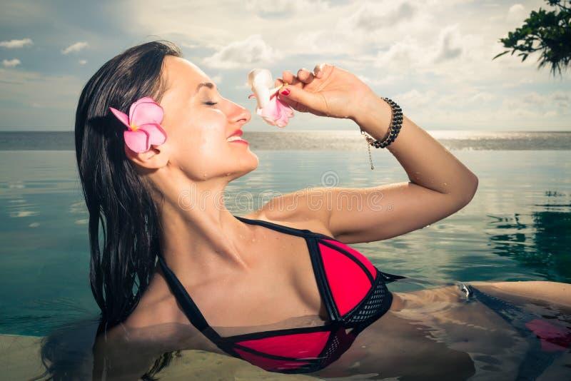Weiblicher Tourist im Unendlichkeitspool des Hotelerholungsortes lizenzfreie stockfotos