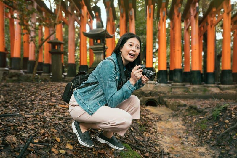 Weiblicher Tourist knien Foto unten, machend lizenzfreie stockfotografie