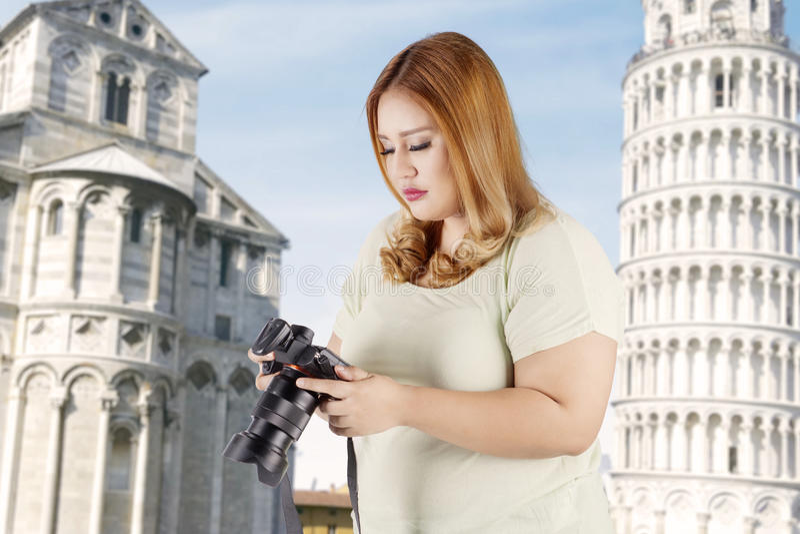 Weiblicher Tourist mit Digitalkamera nahe Turm Pisa lizenzfreies stockfoto