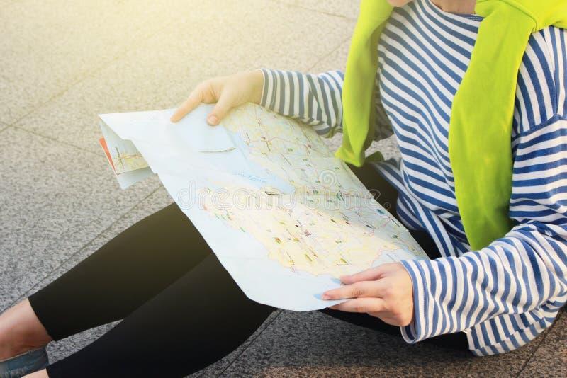 Weiblicher Tourist mit Koffergepäck-Ansichtkarte für Reise auf unterschiedlicher Stadt im Winter, verlorenes allein Konzept stockbilder