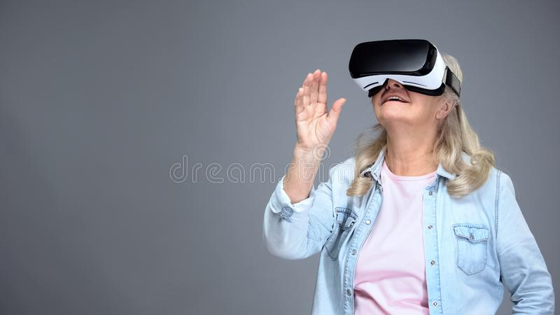 Weiblicher tragender VR Kopfhörer des glücklichen Rentners, moderne Technologien, Innovationen lizenzfreie stockbilder