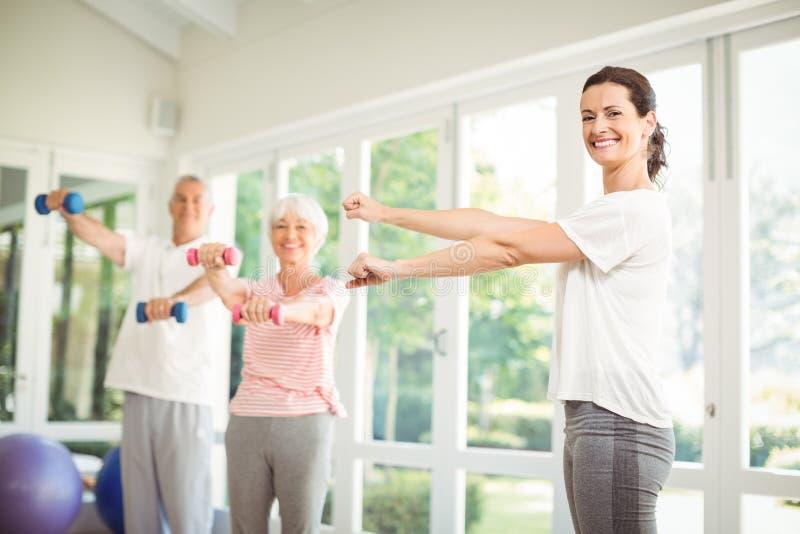Weiblicher Trainer, der ältere Paare unterstützt, wenn Übung durchgeführt wird stockfotografie