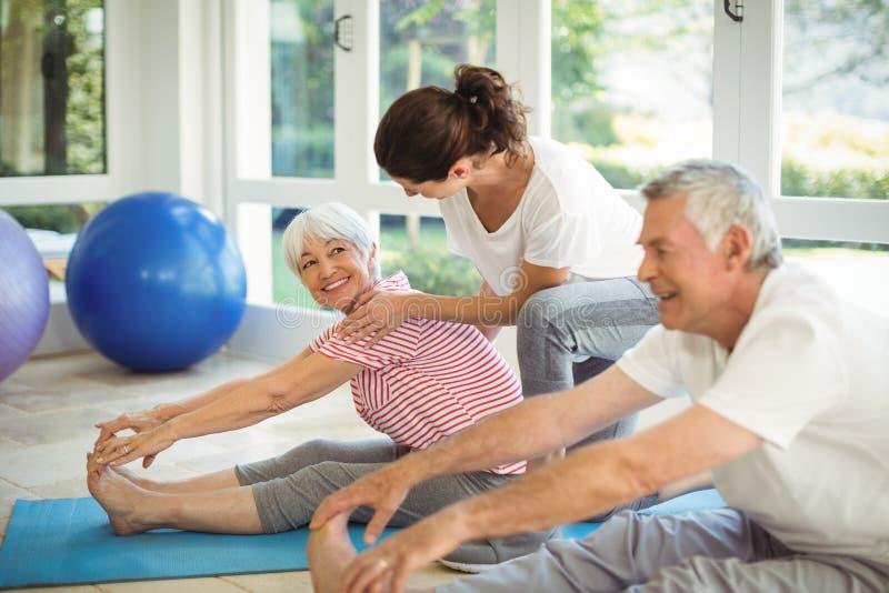 Weiblicher Trainer, der ältere Paare unterstützt, wenn Übung durchgeführt wird stockfoto