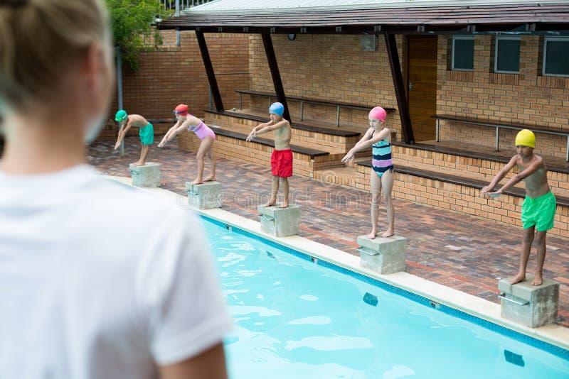 Weiblicher Trainer, der Kinder auf Poolside betrachtet stockfotos