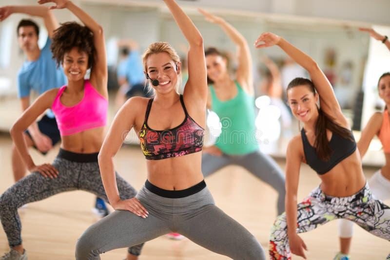 Weiblicher Trainer mit der Eignungsgruppe, die Übungen tut stockfotos