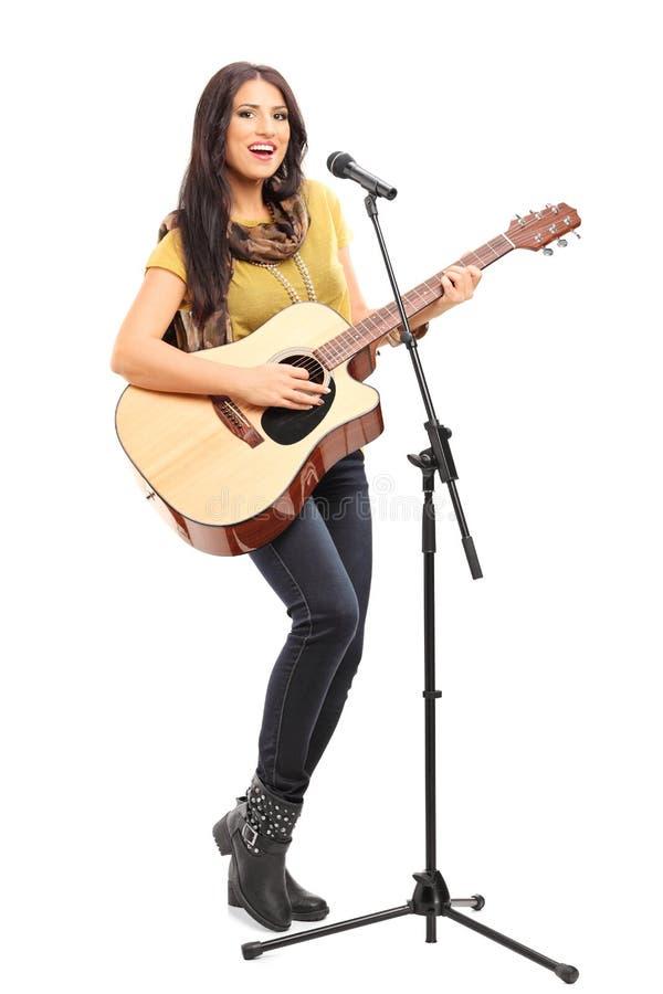 Weiblicher Unterzeichner, der auf Akustikgitarre spielt stockfotografie