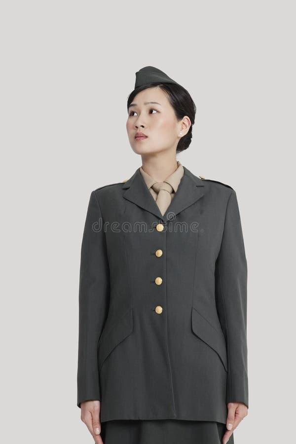 Weiblicher US-Militäroffizier, der in der Aufmerksamkeit steht, wie sie weg über grauem Hintergrund schaut stockbild