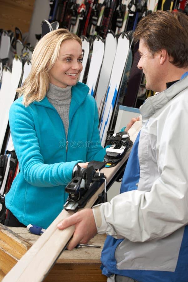 Weiblicher Verkaufs-Assistent, der dem Abnehmer Skis übergibt lizenzfreies stockbild