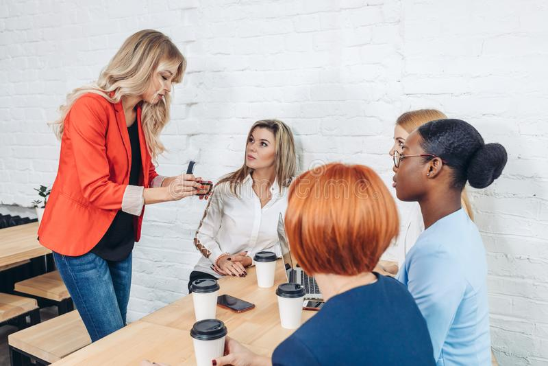 Weiblicher Verkaufs-Berater, der den jungen Geschäftsfrauen über neue Waren spricht stockfotografie