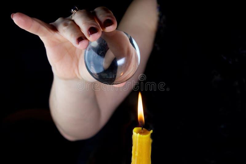Weiblicher Wahrsager, sieht in der Zukunft, indem er in ihre Glaskugel schaut lizenzfreies stockfoto