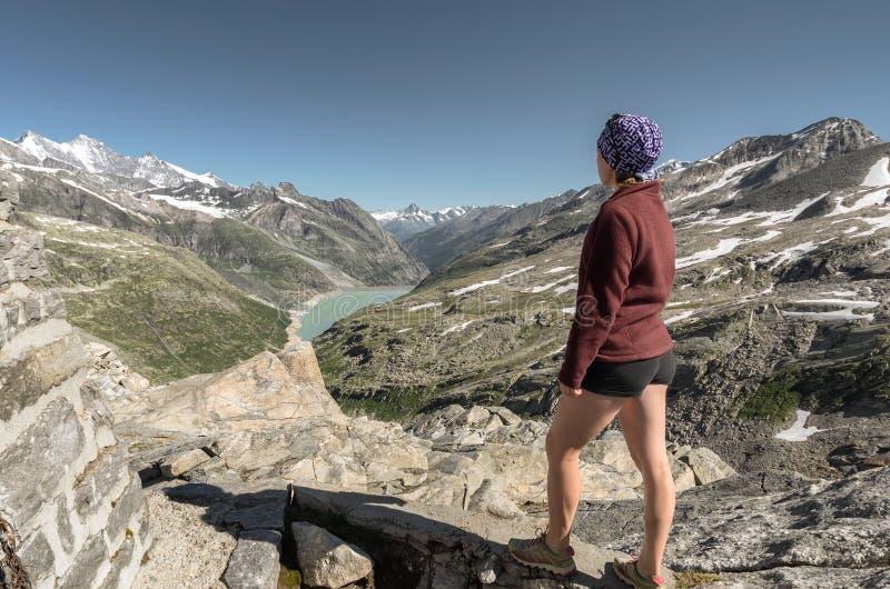 Weiblicher Wanderer, der auf Felsen der Gebirgsgenießenden Spitzenansicht von v steht stockfoto