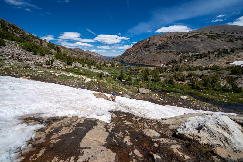 Weiblicher Wanderer, der beunruhigte Kämpfe schaut, um ein steiles Mallschneefeld in der Ostsierra Becken Kaliforniens, 20 Seen o lizenzfreie stockfotografie