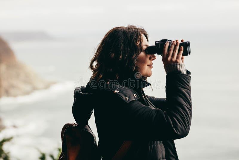 Weiblicher Wanderer, der großartige Ansicht durch Ferngläser genießt lizenzfreies stockbild