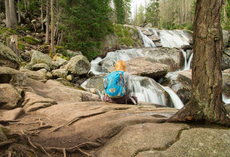 Weiblicher Wanderer, der Wasserfall betrachtet lizenzfreies stockbild