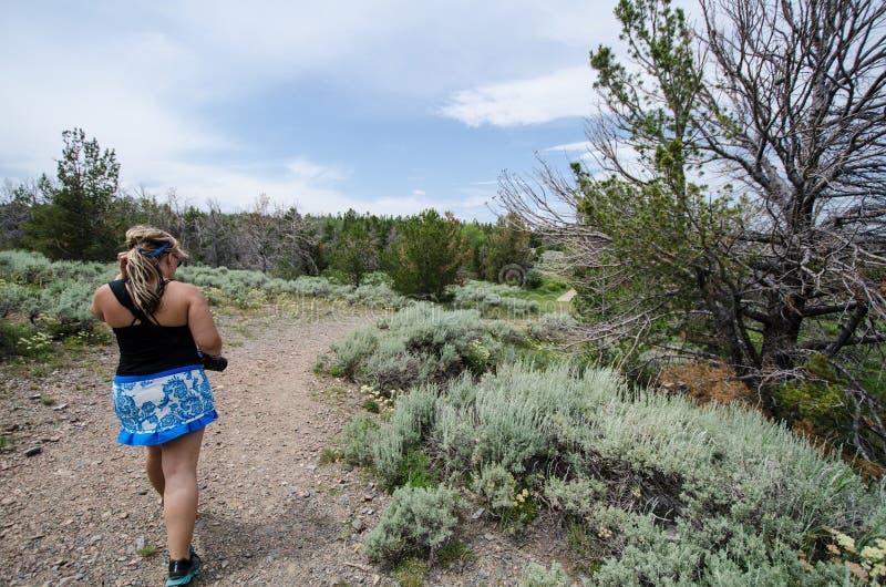 Weiblicher Wanderer geht auf einen Schmutzwanderweg in den Bergmännern erfreuen Wyoming, um eine Geisterstadt zu erforschen lizenzfreie stockbilder