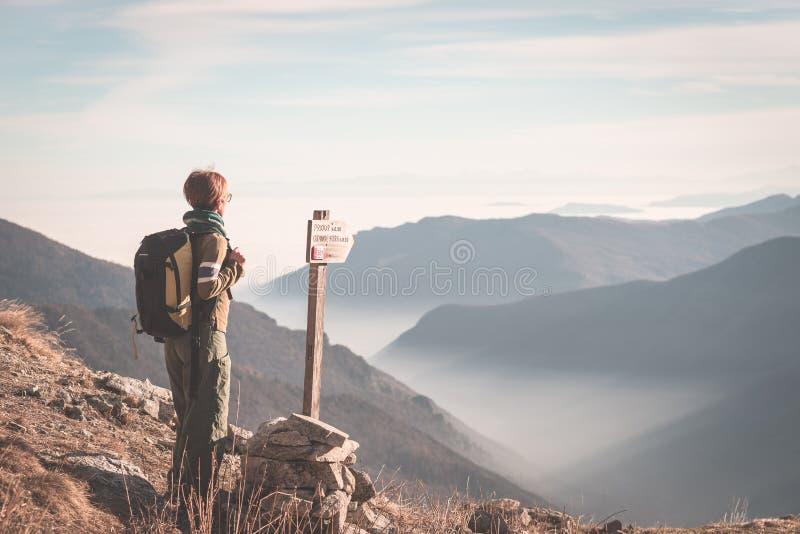 Weiblicher Wanderer mit dem Rucksack, der die majestätische Ansicht über die italienischen Alpen betrachtet Nebel und Nebel im Ta stockfotos