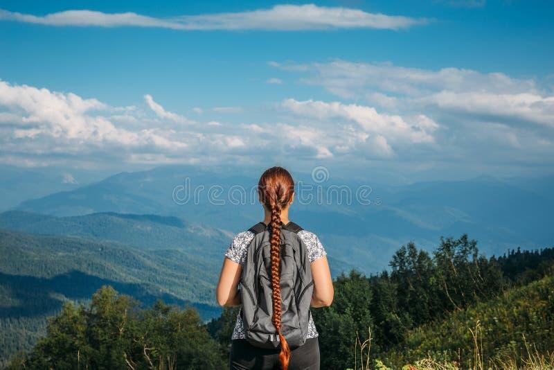 Weiblicher Wanderer mit Rucksack steht auf Berg und schaut zum Tal, Berglandschaft stockfoto