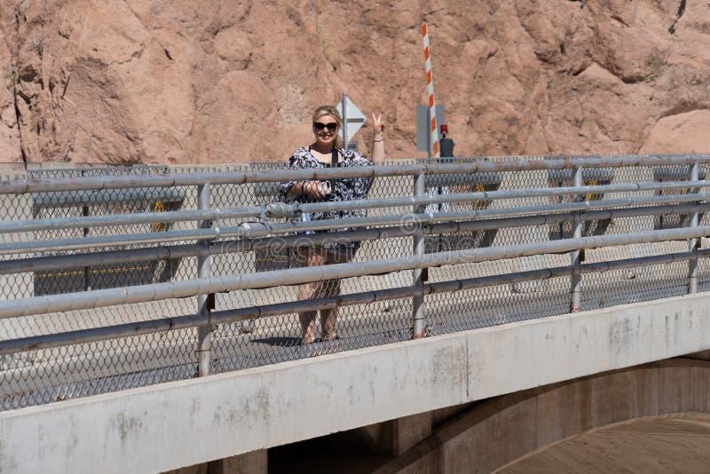 Weiblicher Wandererbesucher zum Hooverdamm lächelt Macht Friedenszeichen stockfotos